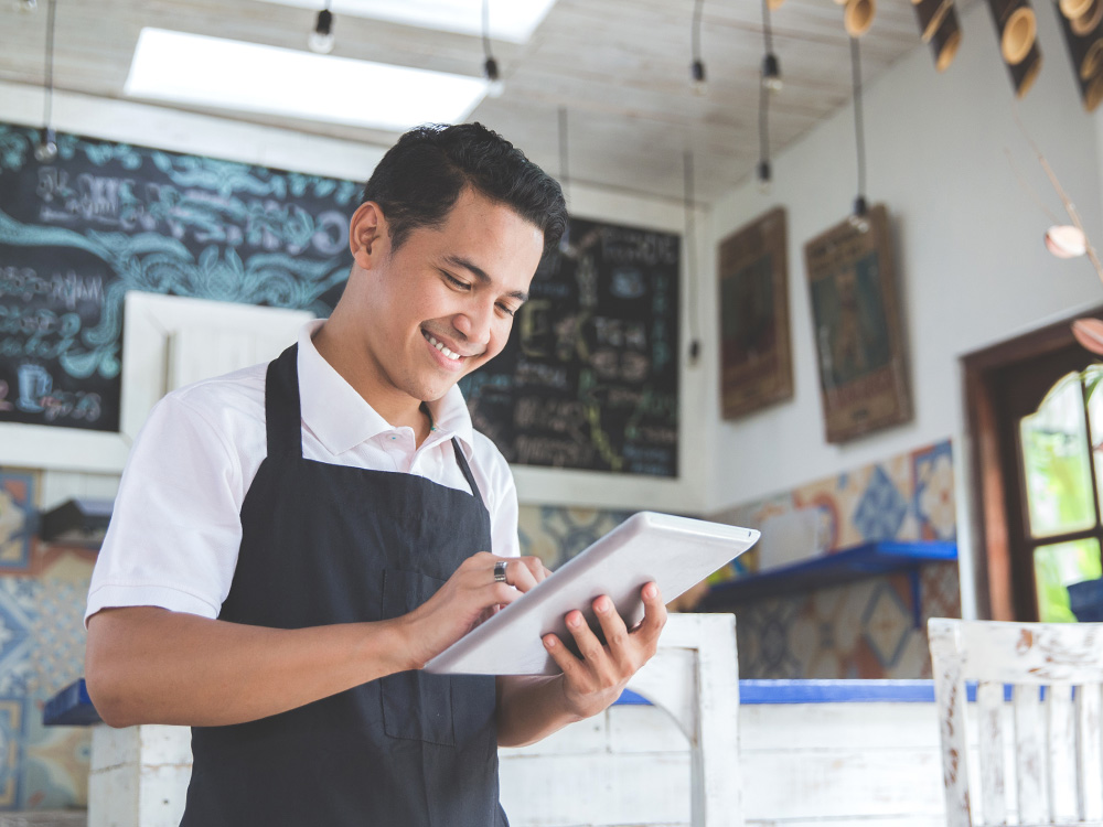Small business owner looking at tablet